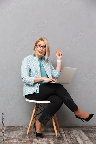 Shocked business woman using laptop computer pointing have an idea Poster