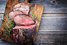 Barbecue Dry Aged Haunch Of Venison With Herbs As Close-up On An Old Cutting Board