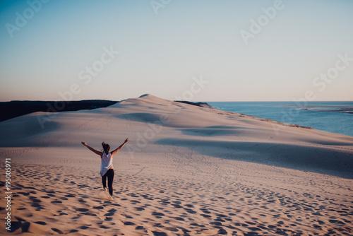 Woman standing on sand and enjoying sun