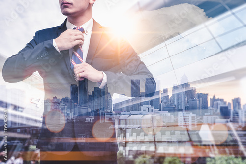 Fototapeta The double exposure image of the businessman wearing the siut during sunrise overlay with cityscape image. The concept of modern life, business, personality, suit, gentleman, formal and lifestyle. obraz na płótnie