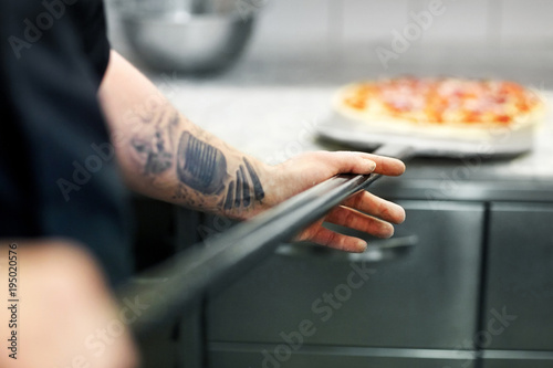 Foto op Canvas Pizzeria cook or baker hand with pizza on peel at pizzeria
