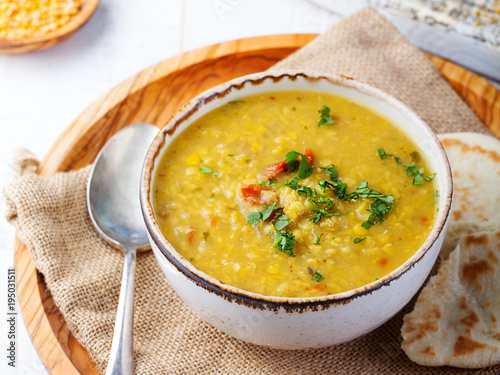Lentil soup with pita bread in a ceramic white bowl on a wooden background Wallpaper Mural