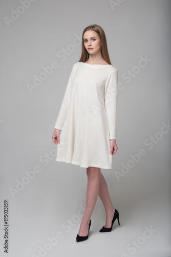 Young beautiful long-haired female model in white dress Fototapeta