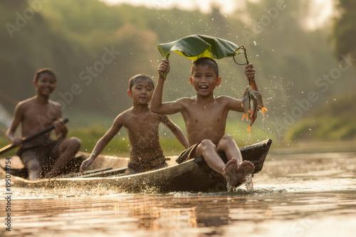 Carta da parati Asia children enjoying in boat on beautiful river