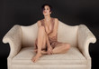 Pretty Woman in Revealing Lace Dress on Couch