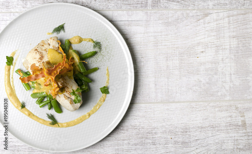 Poster Plat cuisine White fish baked with beans on a white plate