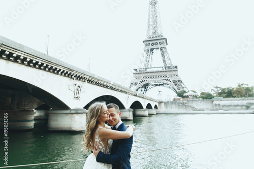 Luxury wedding couple poses before river Seine and the Eiffel Tower somewhere in Canvas Print