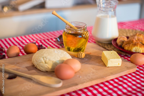 Fresh ingredients are spread out on a wooden board for cooking Poster