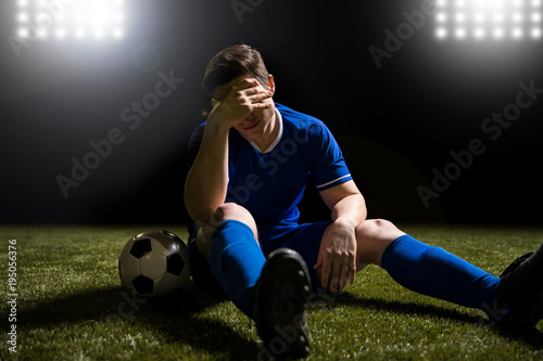 Footballer disappointed sitting on the grass field