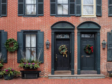 Christmas Decorations Hung On The Doors Of Town Houses