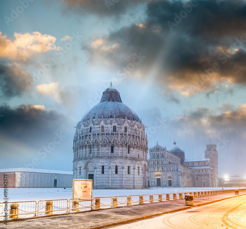Fotografie, Obraz Baptistery of Pisa after a winter snowfall at sunset