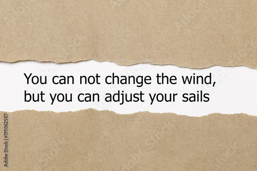 Photo Motivational quote You can not change the wind but you can adjust your sails, appearing behind torn paper