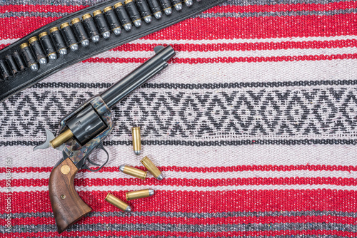 Fotografie, Obraz  Single Action Revolver Reloading Bullets with Gunbelt and Mexican Blanket