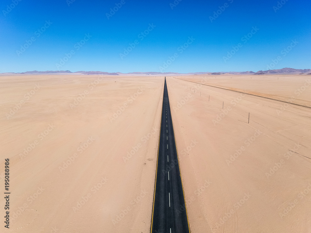 Stunning wide angle aerial drone view of the B4 desert road and a train line between Lüderitz and Keetmanshoop in the Namib Naukluft Desert Park of Namibia, Africa. No curves on the road.