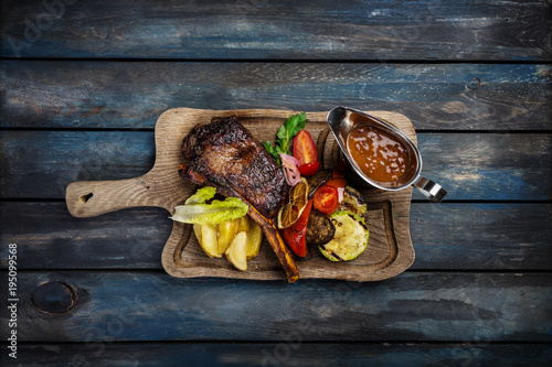 Ribeye steak on bone served with sauce Jack Daniels Canvas Print