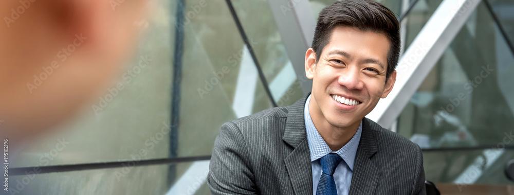 Fototapeta Friendly smiling handsome Asian businessman sitting at office lounge
