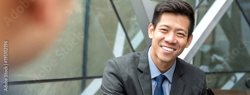 Friendly smiling handsome Asian businessman sitting at office lounge Wallpaper Mural