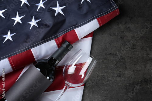 Fotografía  Glass and bottle of wine with American flag on grey background