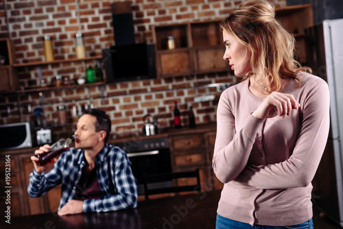 Fotografie, Obraz  selective focus of woman looking at drunk husband at table in kitchen