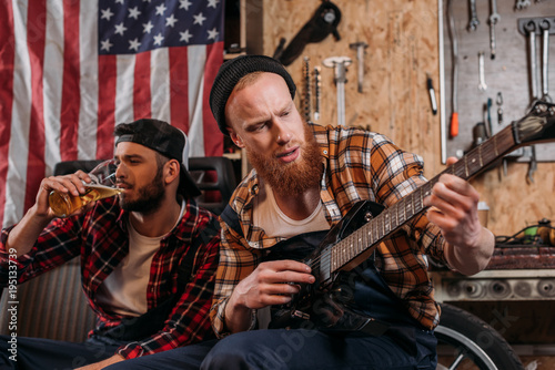 Photo Stands Music Band handsome mechanics playing guitar and drinking beer at garage