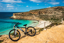 Mountain Bike By The Sea In Lampedusa, A Small Island Close To Africa, Part Of The Pelagie Islands, Sicily. The Rabbit Beach In The Background