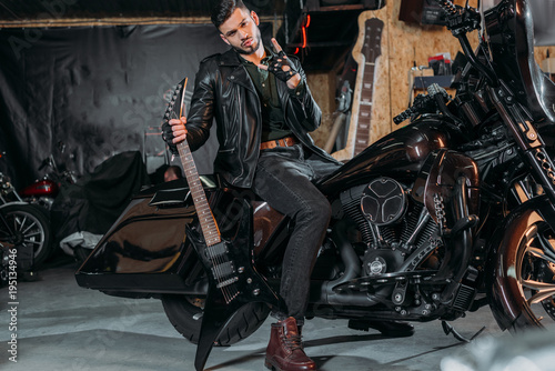 Stylish Young Man In Leather Jacket Sitting On Bike With Electric