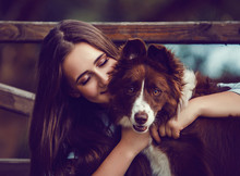 Young Woman And Her Collie Dog In Park, She Is Hugging And Kissing Him. Vintage Style Color.