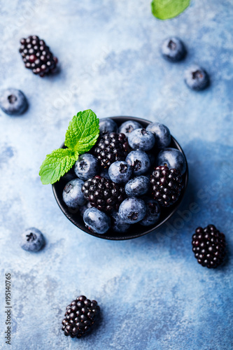 Blueberry and blackberry berries with mint leaves in black bowl on blue stone background. Top view.
