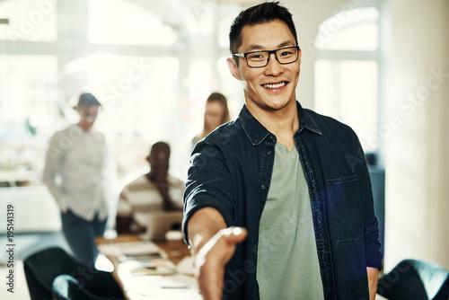 Fotografia  Young Asian businessman standing in an office extending a handshake