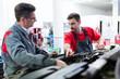 Car mechanics working at automotive service center