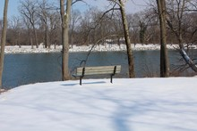 A Empty Park Bench In The Snow Overlooking The River.