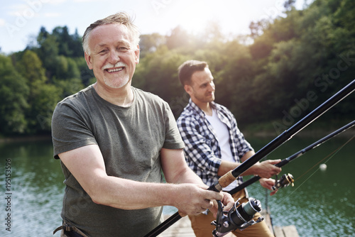 Foto op Plexiglas Vissen Portrait of cheerful senior man fishing .