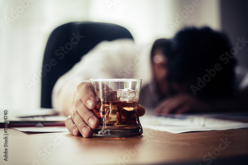 Businessman drinking from stress at workplace - 195164740
