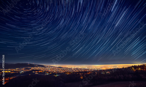 Night sky star trail over the city Canvas Print