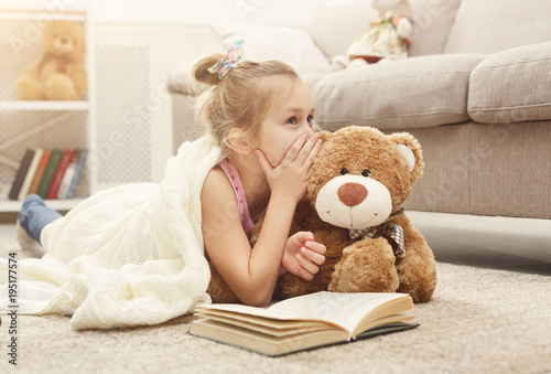 Fotomural Happy little female child and her teddy bear reading book on the floor at home