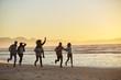 Silhouette Of Friends Having Fun Running Along Winter Beach