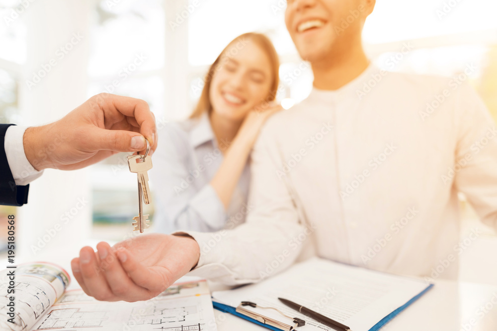 Fototapeta Young couple in a meeting with a realtor. Guy and girl make a contract with realtor buying property.