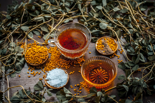 Close up of fenugreek tea with honey,lemon,sugar and fenugreek seeds on a wooden surface in dark Gothic colors.It helps to soothe menstrual cramps, lower blood sugar, promote proper digestion, etc.