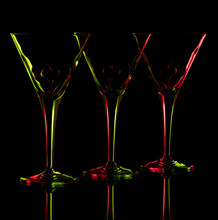 Three Empty Martini Glasses On A Reflective Surface Against A Black Background. It Is Backlit With Green And Red Flashes And There Is A Heart Charm In Each Glass