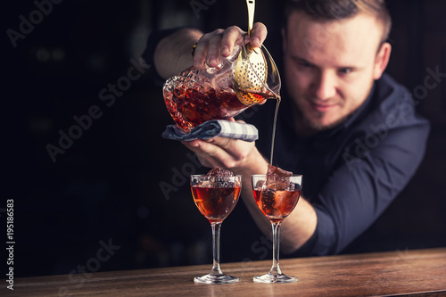 Fotomural  Bartender pouring cocktail alcoholic drink Manhattan.