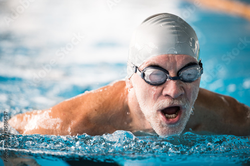 Photo  Senior man swimming in an indoor swimming pool.