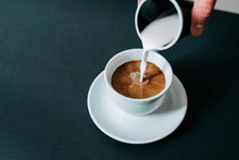 Pouring Creme In Cup Of Coffee. Close-up.