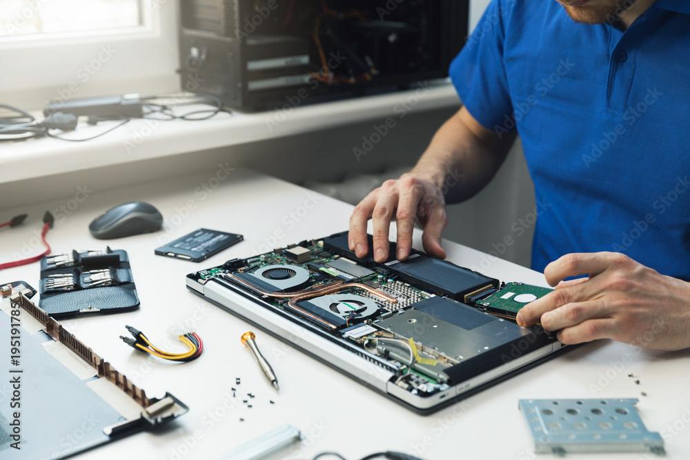 Fototapeta computer repairman installing new hard disk drive in laptop