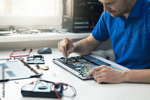 Fotomural computer repair service - technician repairing broken laptop in office