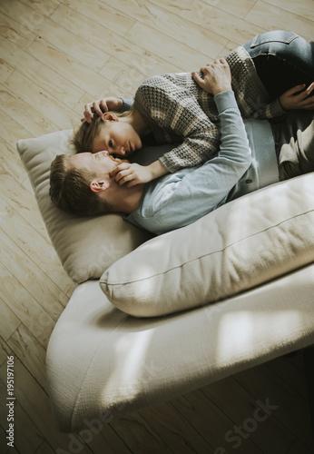 Fototapeta Loving couple lying down on the sofa in the room obraz na płótnie