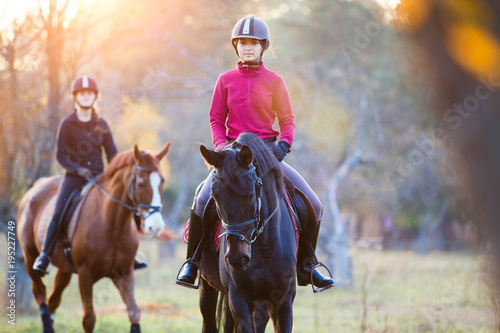 Poster Horseback riding Group of rider girls riding their horses in park. Equestrian recreation activities background with copy space