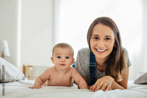 Portrait of a young mother taking care of her cute baby at home.