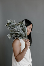 Woman Standing Profile To Grey Wall Wearing White Holding Soft Feathery Plant Over Shoulder