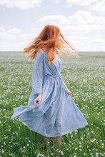 Young Redhead Woman In Blue Dress Swirl In The Summer Meadow