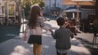 Two kids walk together, hold hands. Slow motion. Back view. Little children explore old town streets on a sunny day.